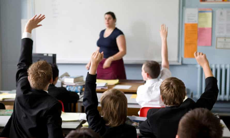 Pupils put their hands in the air to answer a question in a lesson