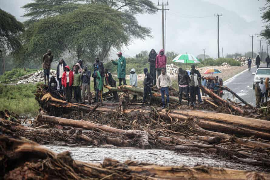 People stand on debris blocking a highway after River Muruny burst its bank following heavy rains in Parua village, in Kenya's West Pokot county