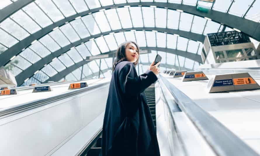 Low angle view of confident Asian woman checking emails on smart phone, riding an escalator, commuting to work.