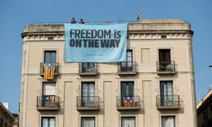 Catalonia independence supporters unfurl a banner on a building next to the Palau de la Generalitat, the regional government headquarters, in Barcelona, on Friday.