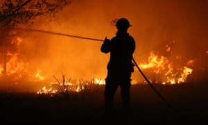 A firefighter battling a bushfire on the NSW south coast on Thursday. Smoke from the fires will contribute to a massive global rise in carbon dioxide concentrations in the atmosphere.