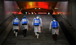 Workers with sanitising equipment walk up a flight of stairs as they disinfect a railway station in Kunming, Yunnan province, China.
