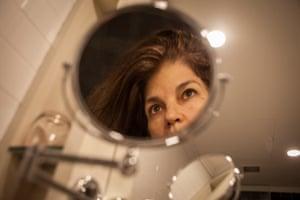 Self-portrait of Jillian Edelstein in hotel makeup mirror