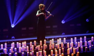 Lindsey Stirling playing violin in front of candles