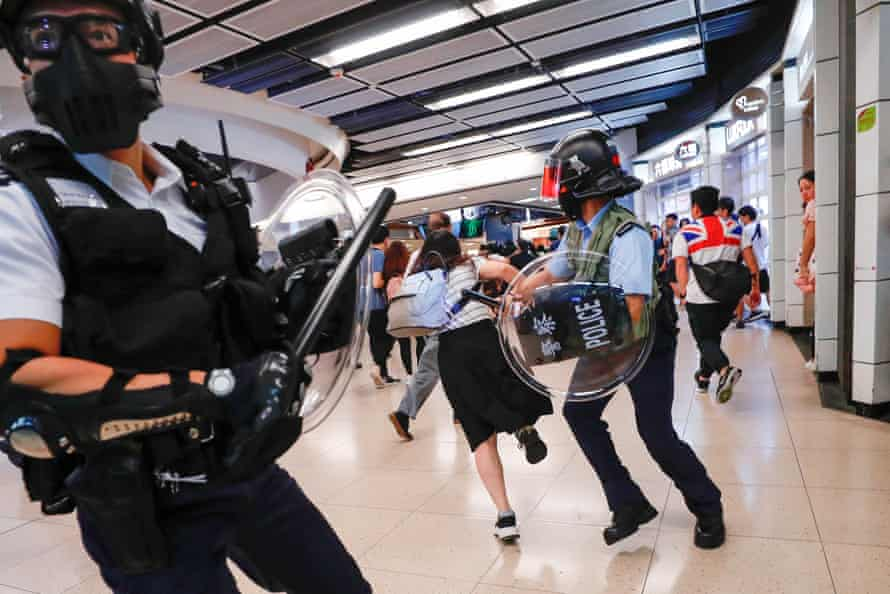 Anti-government protesters run away from riot police as they gather at Sha Tin Mass Transit Railway (MTR) station to demonstrate against the railway operator, which they accuse of helping the government, in Hong Kong, China September 25, 2019.