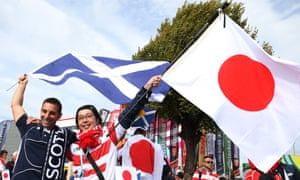 A Scotland supporter and a Japan fan fly their flags before their Rugby World Cup match at Kingsholm in September