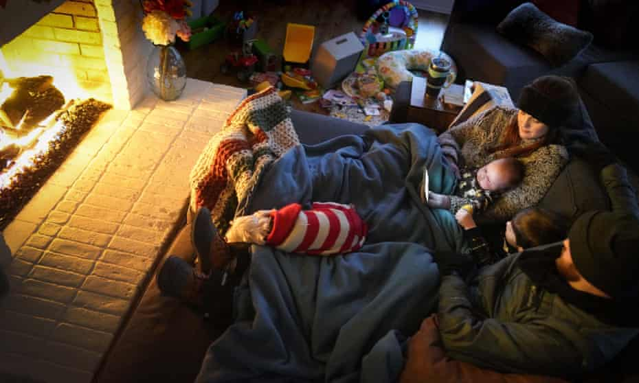 Dan and Anna Bryant huddle by the fire with sons Benny, 3, and Sam, 12 weeks, and their dog, Joey, with power out in Garland, Texas, on Monday.