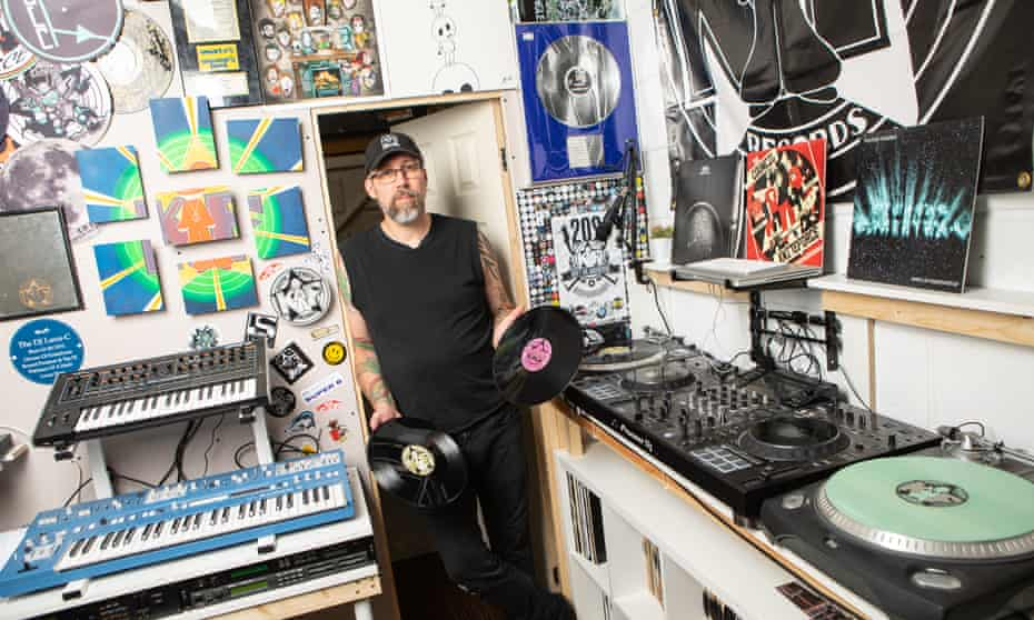 Producer and DJ Chris Howell, also known as Luna-C, in his studio, holding two vinyl records.