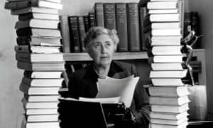 A lot to choose between … Agatha Christie sitting behind her desk with copies of her books piled around her.