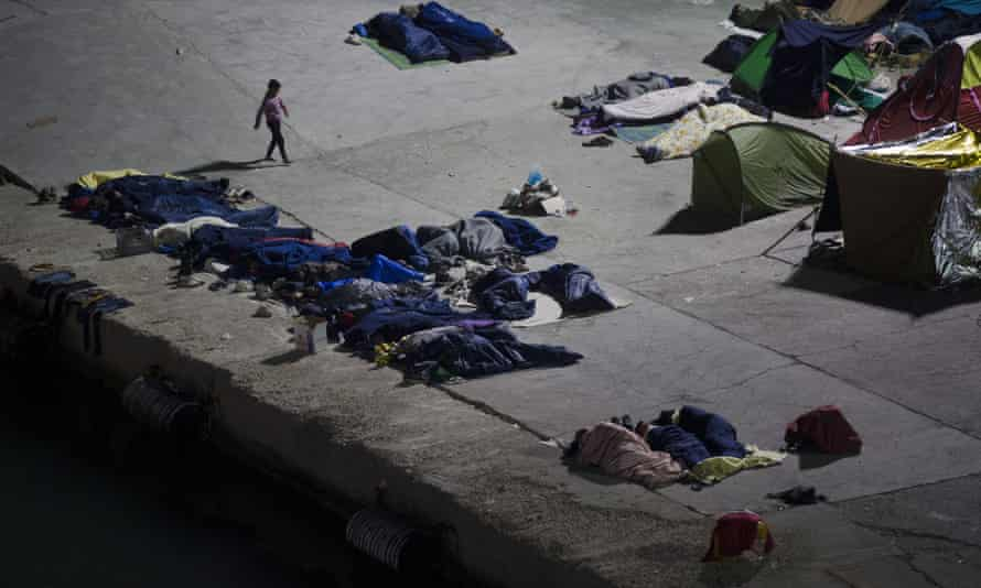 People sleep at the port of Chios island, Greece.