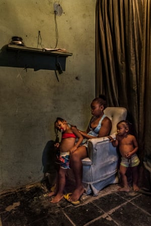Inside one of the basic favela homes a mother braids the hair of one of her daughters. Despite being marginalised and blamed for many of Rio's social problems, the residents of the favela have created a society based on co-operation to survive in the overpopulated city