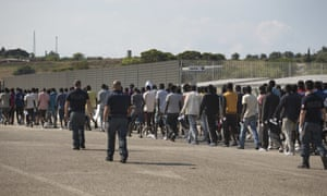 Italian border police with crowd of men