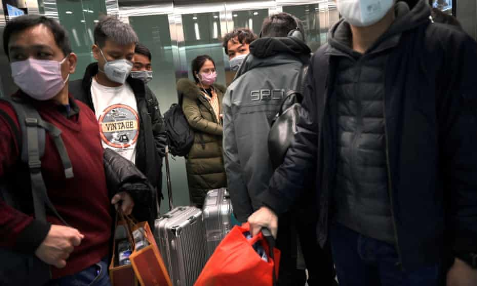 People arriving at the Beijing Daxing international airport wear protective face masks