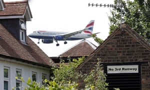 A sign in the village of Longford reads 'No 3rd Runway' as a British Airways plane prepares to land at Heathrow airport.