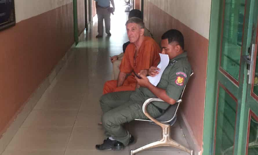 Australian Garry Mulroy (in orange) is seen before a court hearing in Phnom Penh, Cambodia in March. He has flown out of the country after being released from jail on appeal.