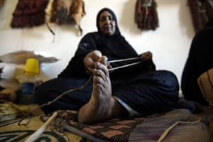 Cheynoune Zeineb, a Tuareg and imzad instrument maker, holds a chord of horse hair whose far end is lodged between her toes while making a new imzad
