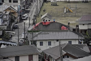 People clean volcanic ash from the red roof of a home in Wallilabou.