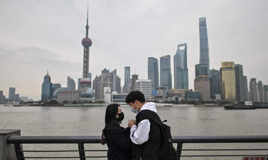 A couple visits the promenade on the Bund along Huangpu River in Shanghai