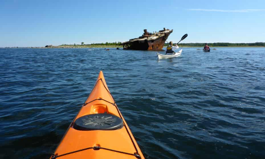 Kayakers approaching the wreck used for Soviet target practice.