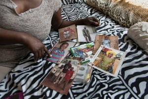 A woman displays photos of relatives from Nigeria.