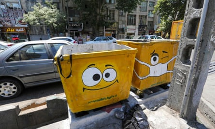 Two large litter bins with cartoon faces painted on them, one of the faces wearing a mask
