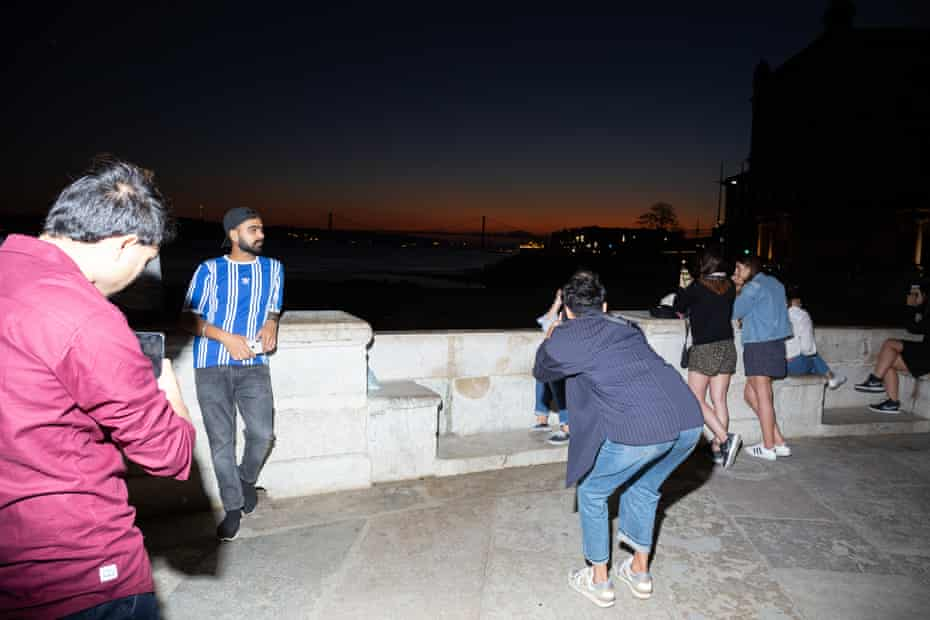 Tourists flock to the water at sunset to take photos.