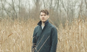 Joel Golby standing in a field of tall, pale corn or grass in winter