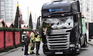Firefighters inspect the truck that crashed into a Christmas market in Berlin.