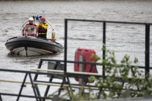 The fire and rescue service search the River Taff using a boat after reports a woman had fallen into the water in Cardiff, Wales