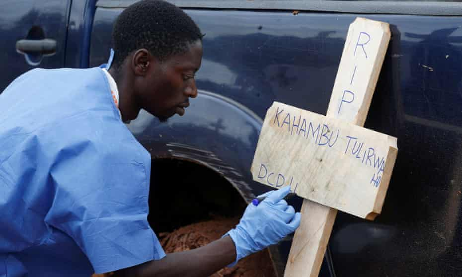 A Congolese Red Cross worker writes on a cross the name of Kahambu Tulirwaho, who died of Ebola, before a burial service at a cemetery in Butembo