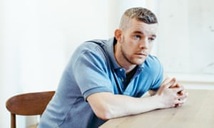 Russell Tovey in a pale blue polo shirt, sitting at a table, leaning forwards