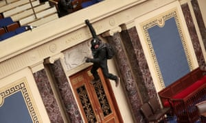 A protester is seen hanging from the balcony in the Senate Chamber in Washington, DC.