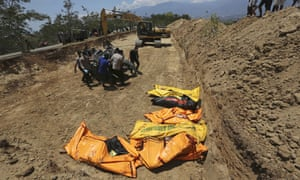 Indonesian police carry the body of a tsunami victim during a mass burial in Palu, Central Sulawesi