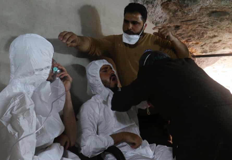 A man breathes through an oxygen mask as another one receives treatment.