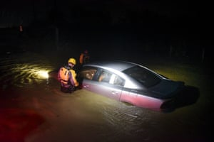 Rescue staff from the Municipal Emergency Management Agency investigate a flooded car in Fajardo, Puerto Rico
