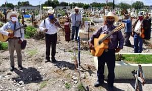 Muzicienii din grupul Los Tigres de la Guasteca îi cântă decedatului în panteonul San Isidro, în municipiul Ecatepec, Mexic.