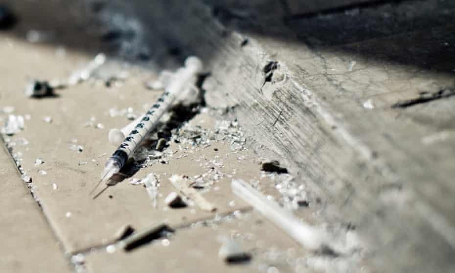 broken syringes on pavement