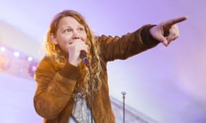 Kate Tempest on stage, holding a microphone in one hand and pointing ahead with the other