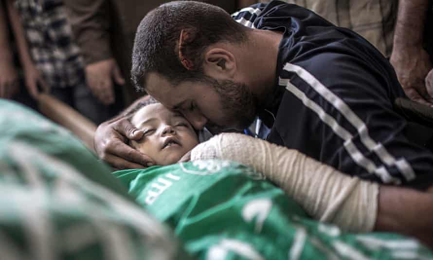 Yehiya Hassan cries with the bodies of his two-year-old daughter and wife