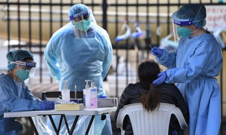 Healthcare workers test a woman for coronavirus