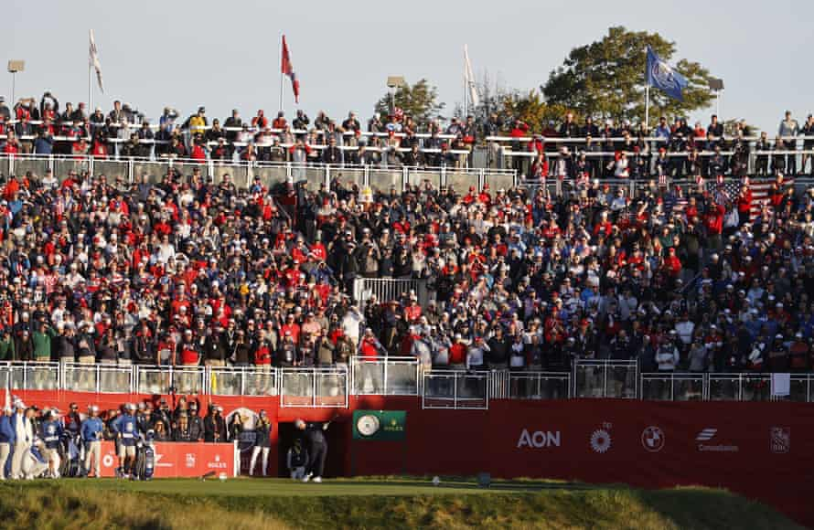A packed grandstand watches Collin Morikawa hit his opening tee shot.
