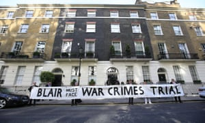 Protesters hold a banner outside the London home of Tony Blair