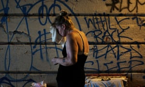 A woman who is homeless and an addict under a bridge where she lives in the Kensington section of Philadelphia on 21 July 2017.