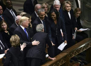 George W Bush leans over to shake hands with Michelle Obama.