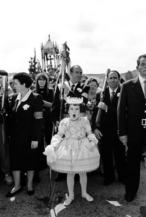 A young girl in a princess dress and crown yawning, adults gathered behind her
