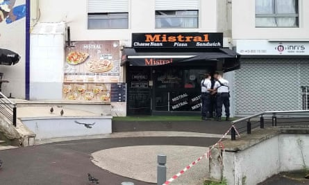 Policemen stand in front of the eatery where a waiter was shot dead by a customer allegedly angry at having to wait for a sandwich, in the eastern Paris suburb of Noisy-le-Grand.
