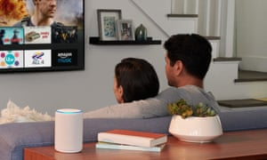 A couple watch a smart TV with an Amazon Echo speaker in the foreground