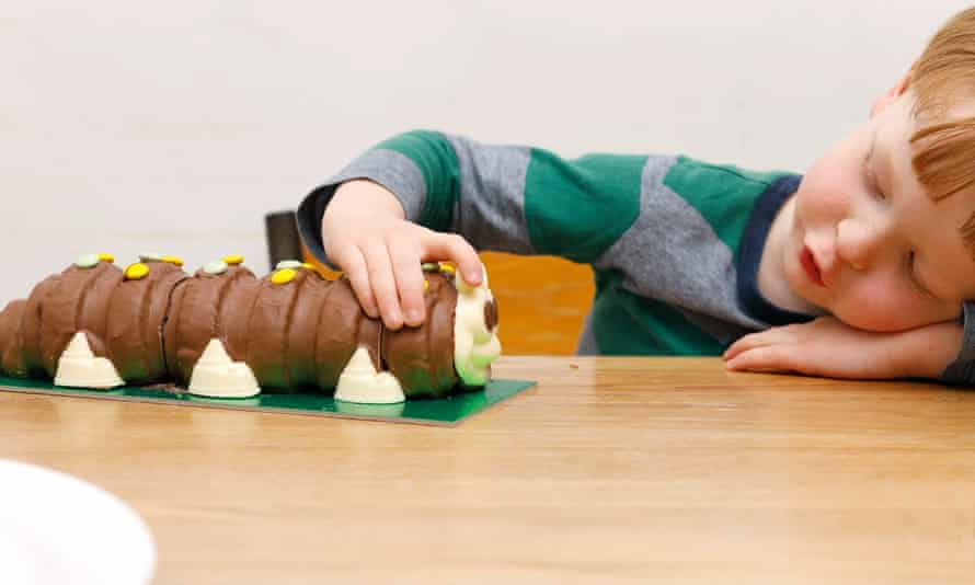 A little boy with Colin the Caterpillar cake.