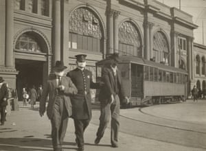 A police officer wearing a flu mask leads two men away from the Ferry building in San Francisco in 1918.