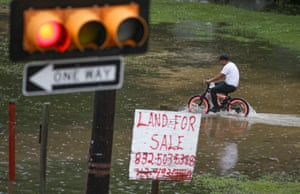A boy on a bike rides in the flooded waters on 19 September 2019 in Houston, Texas.